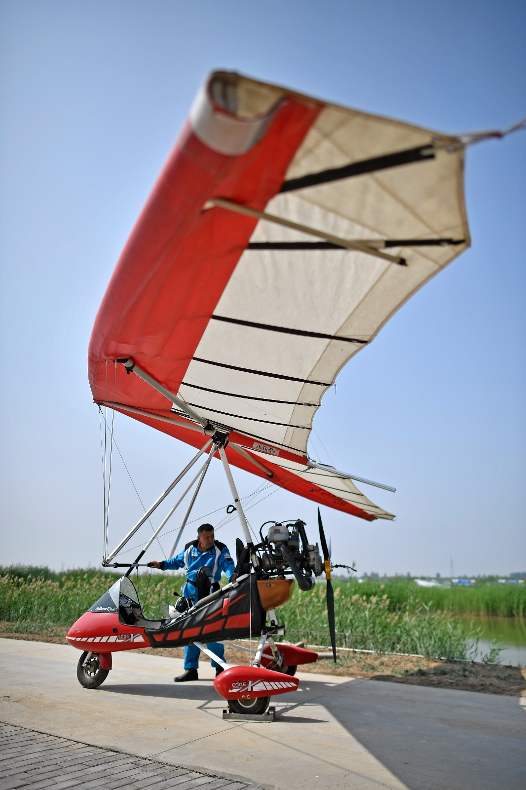 """刘亦兵在飞行前对动力三角翼飞机进行检查(6月21日摄)。 46岁的刘亦兵是银川市贺兰县一处飞行营地的动力悬挂滑翔飞行教练。17岁初中毕业在家务农的刘亦兵偶然看到一本飞行杂志,萌发了自制飞机的念头。多年间,刘亦兵对飞机制造方法不断摸索,自学相关航空知识,终于在1996年,第一次驾驶自制飞机飞上蓝天。  之后他考取了动力三角翼飞行执照,在亲友的帮助下购买了二手动力伞和动力三角翼,并进行了很多商业尝试。在航空运动方面,刘亦兵多次在飞行比赛中获奖,还被选为中国航空运动协会飞行队队员,考取了动力悬挂滑翔飞行教练执照。 2010年,刘亦兵在宁夏贺兰县承租了一块土地,成立航空俱乐部,建造了停机库及跑道。刘亦兵说,""""我从一个啥都不懂的农民,到自己制造和驾驶飞机,并成为一名飞行教练,过程非常艰难。我希望我的经历能激励航空爱好者和推动航空运动的发展,促进更多人了解航空知识""""。新华社记者 王鹏 摄"""